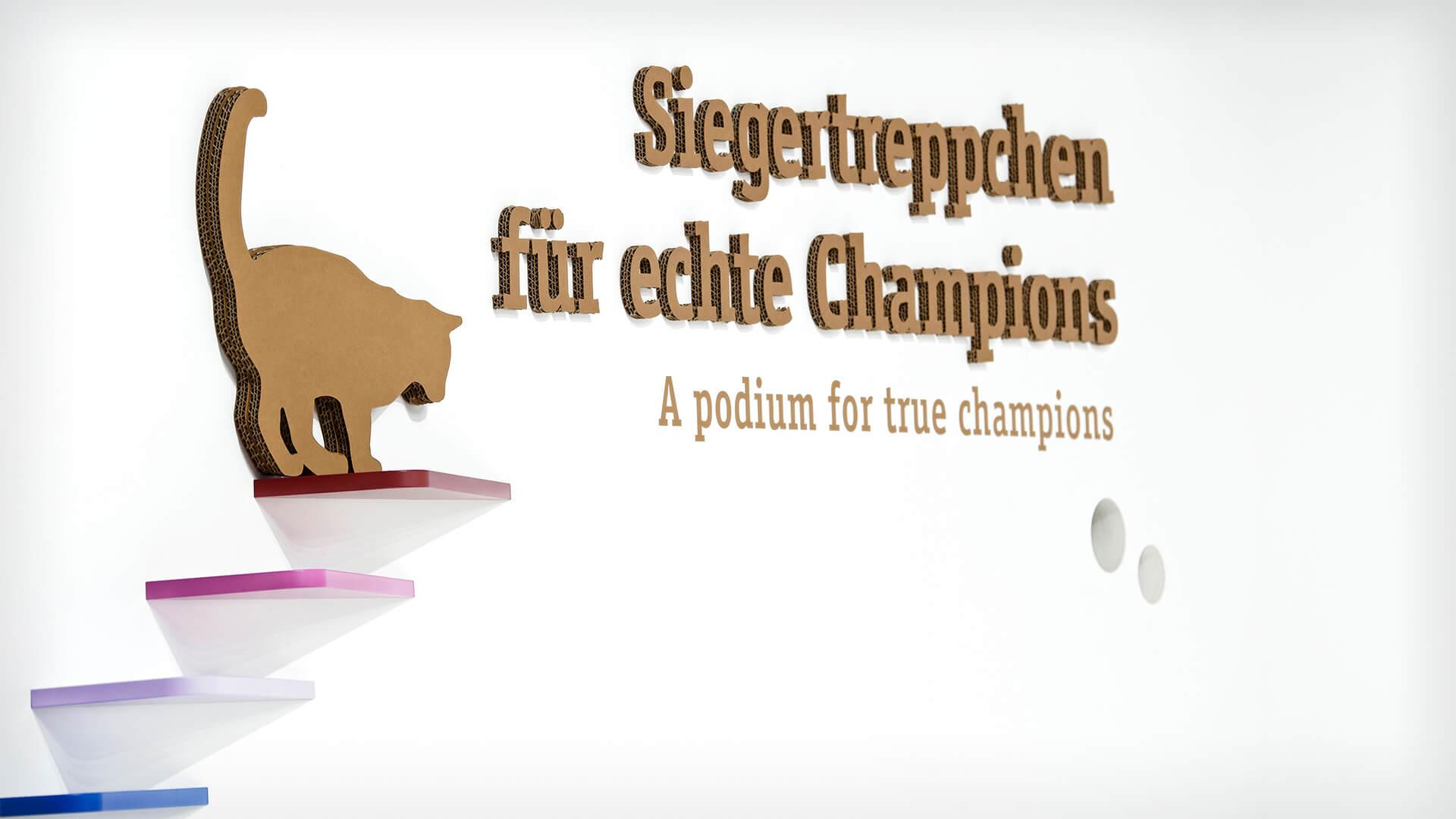 Messedesign auch für die Wand: Pappkatze auf Papptreppe, Schriftzug: Siegertreppchen für echte Champions