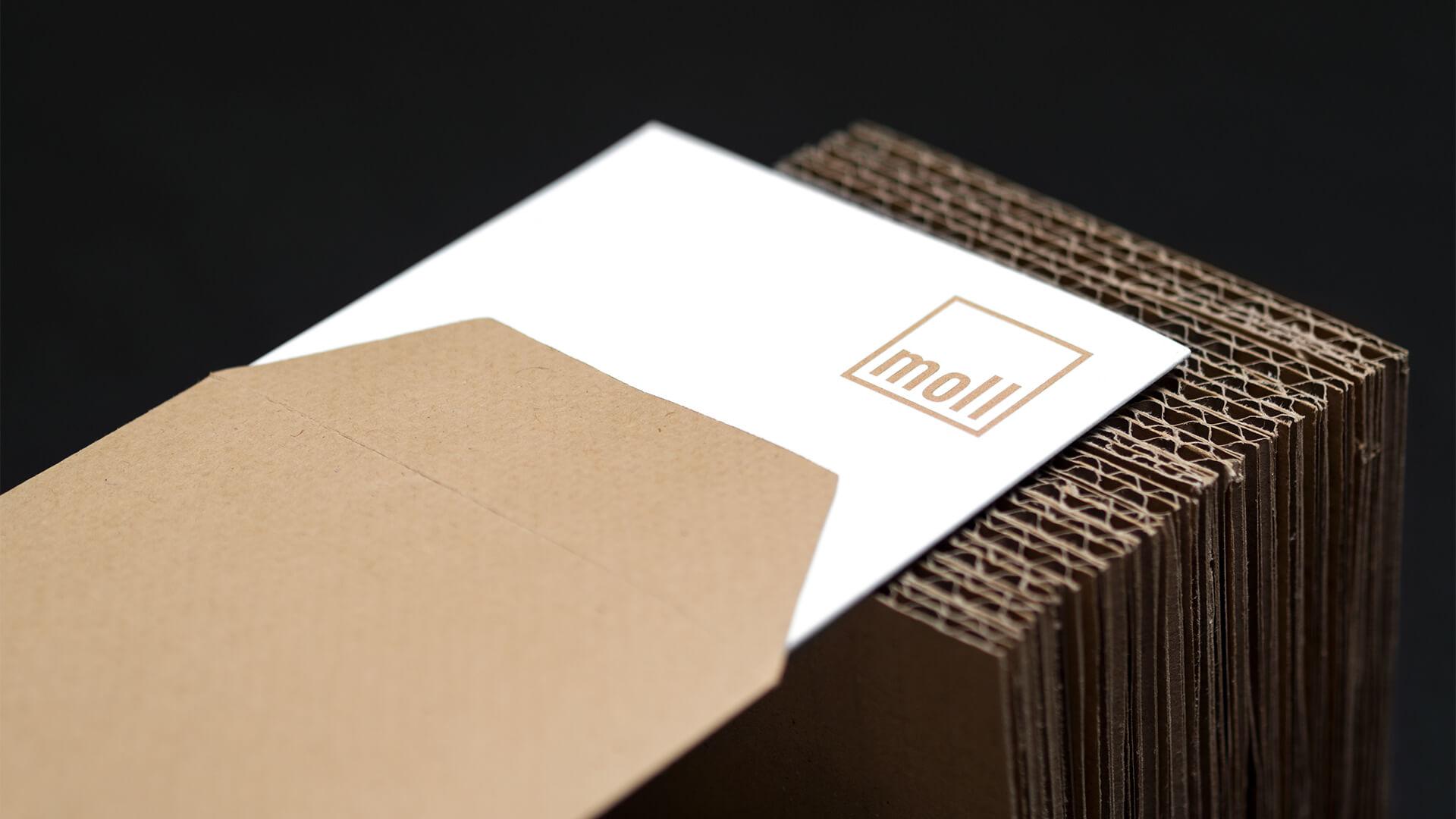 Die Einladungskarte zur Messe halb herausgezogen aus dem Papierumschlag mit Logo moll