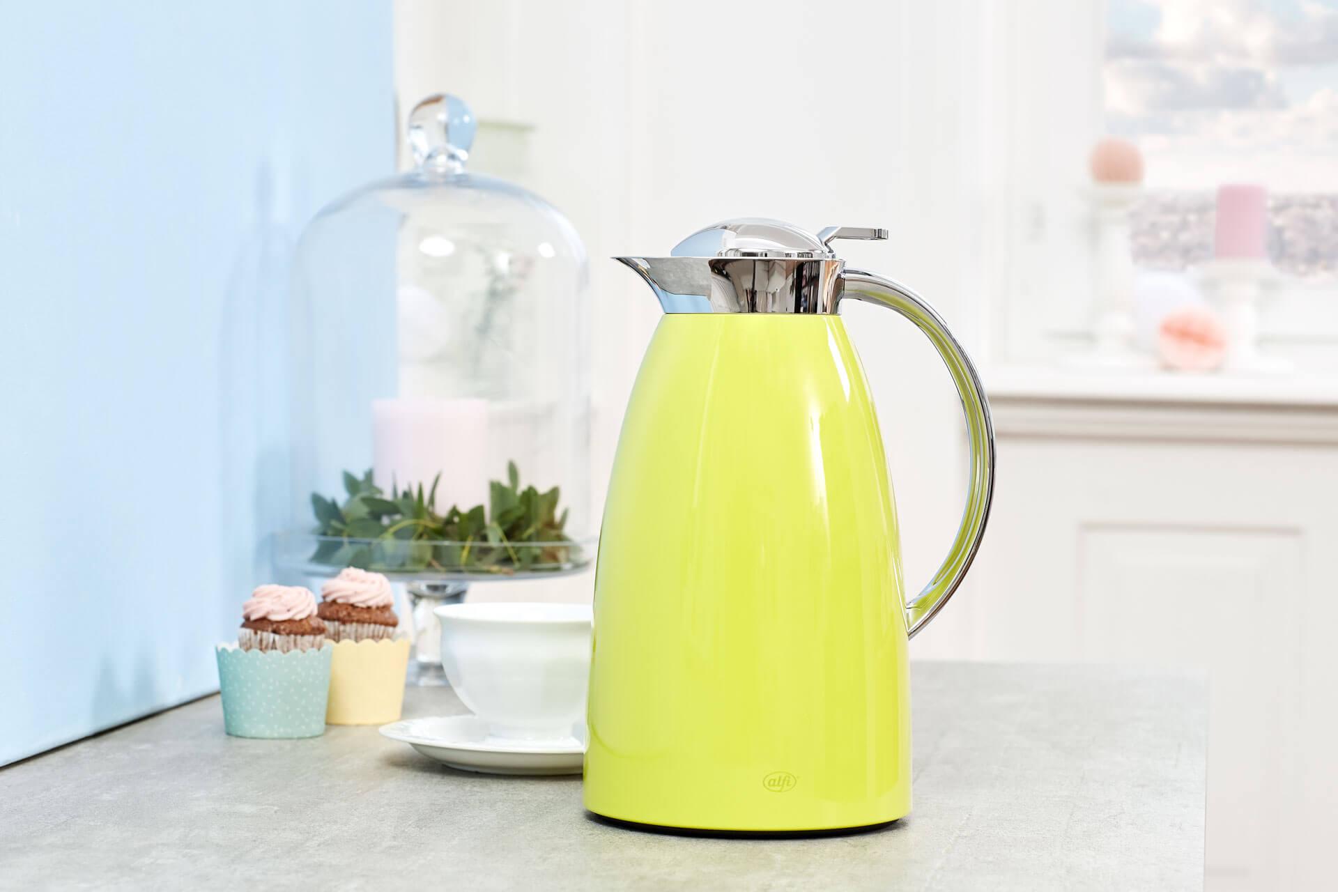 Markteinführung der grünen Gusto von alfi: Kanne in frischer Farbe auf Sideboard vor Kaffeetasse und Muffins.